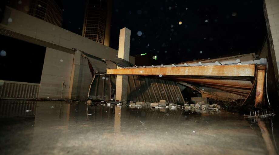 A garage with walls collapsed by the winds of Hurricane Harvey is seen in downtown Corpus Christi, Texas, Saturday, Aug. 26, 2017.  Harvey has been further downgraded to a Category 1 hurricane as it churns slowly inland from the Texas Gulf Coast, already depositing more than 9 inches of rain in South Texas. (AP Photo/Eric Gay) Photo: Eric Gay, STF / Copyright 2017 The Associated Press. All rights reserved.