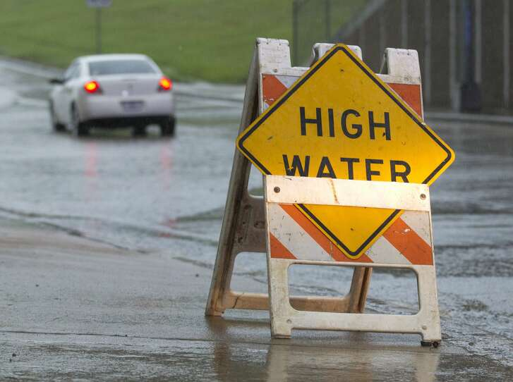 A sign warns drivers of high water on the east bound side South Loop 336 near Frazier Street after a woman drove her car through high water, Saturday, Aug. 26, 2017, in Conroe.