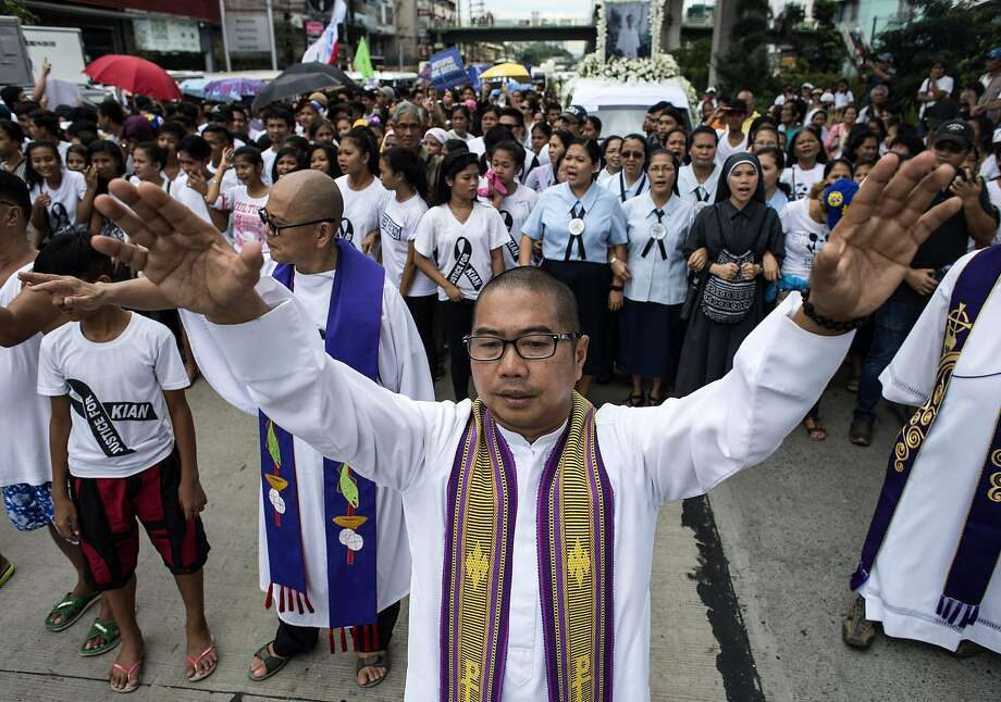 A priest gestures during the funeral march for 17-year-old student Kian Delos Santos, who was killed allegedly by police officers during an anti-drug raid, in Manila on August 26, 2017.  Thousands of Filipinos called for an end to extrajudicial killings as the funeral of a boy killed by police turned into the largest single demonstration yet against President Rodrigo Duterte's brutal drug war. / AFP PHOTO / NOEL CELISNOEL CELIS/AFP/Getty Images Photo: NOEL CELIS, AFP/Getty Images