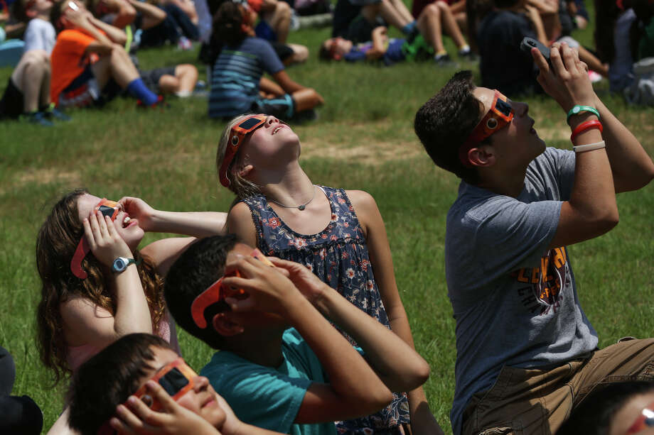 Mitchell Intermediate sixth graders snap photos while looking at a partial solar eclipse last week at Mitchell Intermediate School in The Woodlands.(Michael Minasi / Houston Chronicle) Photo: Michael Minasi, Staff Photographer / Internal