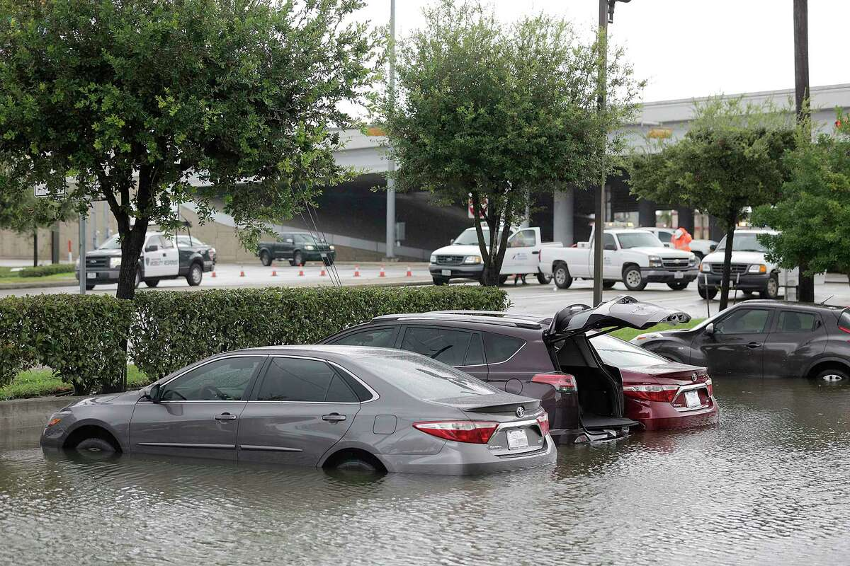 Cars left overnight at Amergy Bank parking lot float as the water rises on Bellfort Ave., while it continues to flood as a result of Hurricane Harvey on Saturday, Aug. 26, 2017.