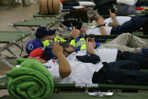 First responders get some rest Saturday August 26, 2017 in a building near the Freeman Expo Hall as Hurricane Harvey passes through San Antonio.  The area is a staging hub for emergency personnel from all over the United States and is a temporary home for emergency wokers from Texas, Missouri, Ohio, Utah and other states. The storm is moving to the north.