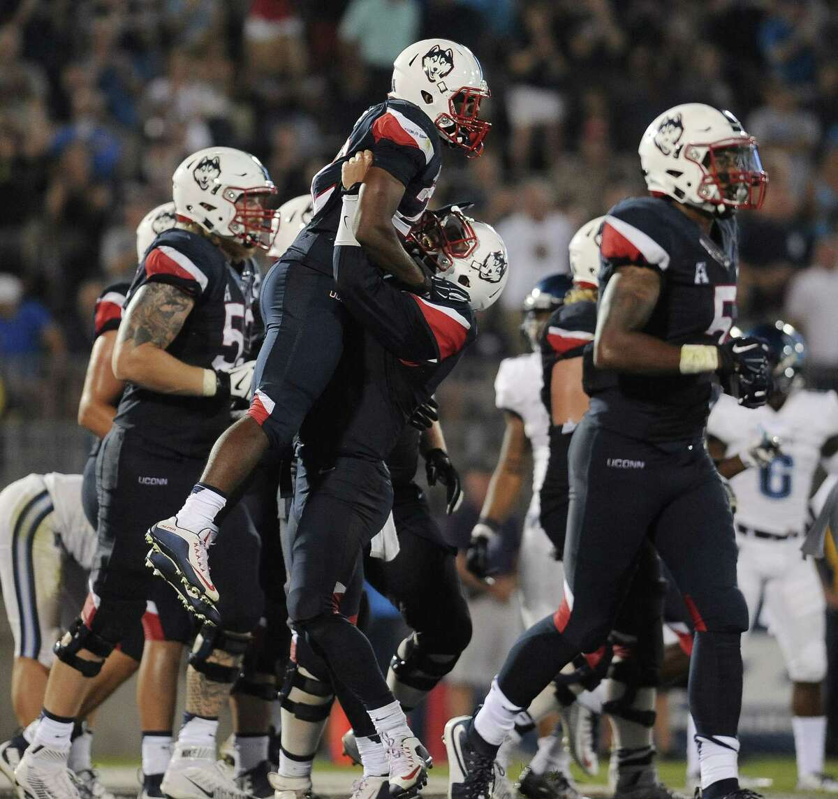 Connecticut running back Arkeel Newsome is lifted into the air by Connecticut quarterback Bryant Shirreffs after Newsome scored a touchdown during the second half of an NCAA college football game at Rentschler Field, Thursday, Sept. 3, 2015, in East Hartford, Conn. UConn won 20-15. (AP Photo/Jessica Hill)