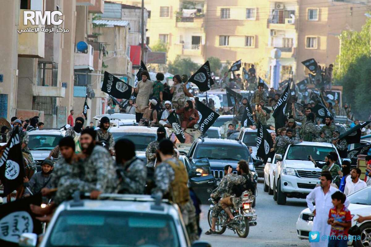 In this undated file image posted by the Raqqa Media Center of the Islamic State group, a Syrian opposition group, fighters from the Islamic State group parade in Raqqa, northern Syria.