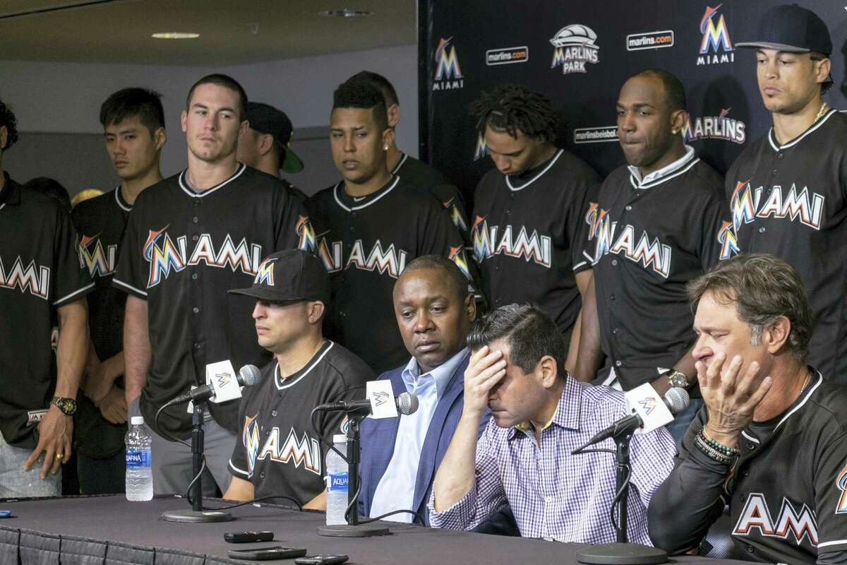 David P. Samson, center, president of the Miami Marlins, covers his face during press conference to announce the death of Marlins pitcher Jose Fernandez.