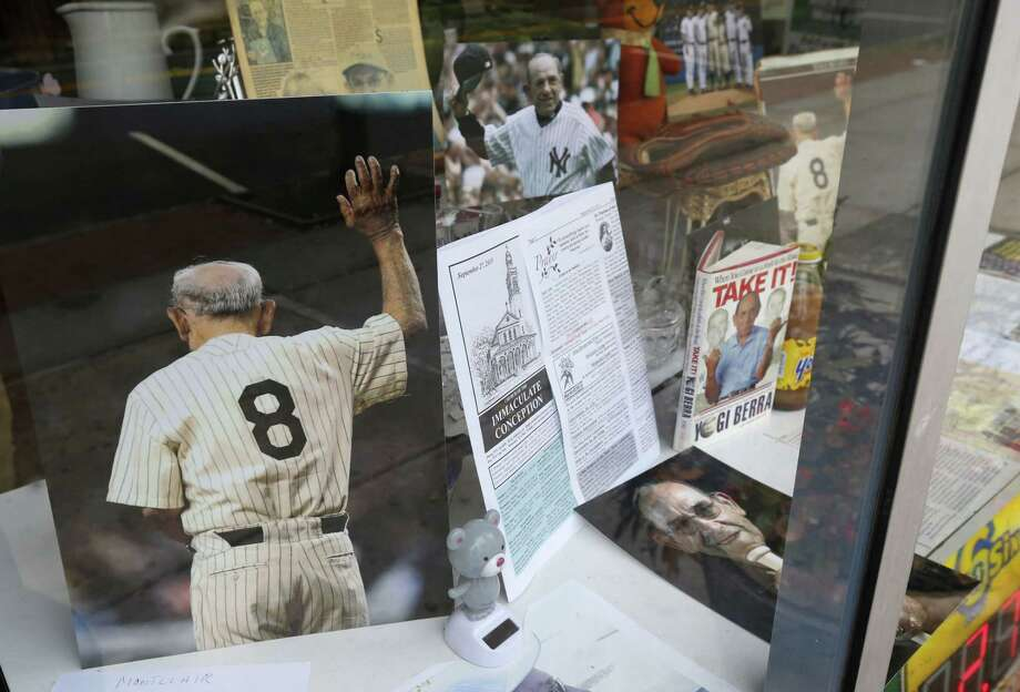 Memorabilia of New York Yankees Hall of Fame catcher Yogi Berra is on display at a store near Church of the Immaculate Conception before funeral services for the late baseball star, Tuesday, Sept. 29, 2015, in Montclair, N.J. The baseball legend known for his quirky sayings died Sept. 22. He was 90. (AP Photo/Julio Cortez) Photo: AP / AP