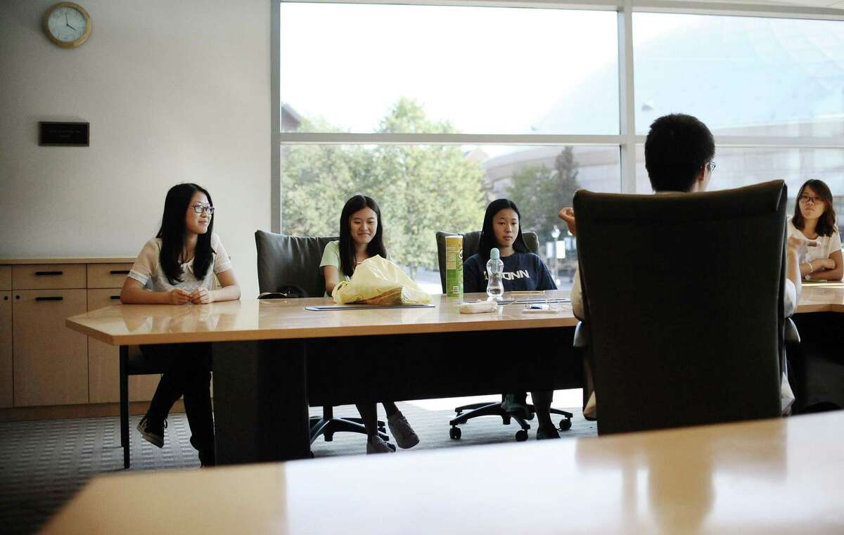 In this Friday, Sept. 18, 2015 photo, University of Connecticut sophomore, Anyi Yang of Beijing, left, attends a meeting of the Chinese students and scholars association on campus in Storrs, Conn.