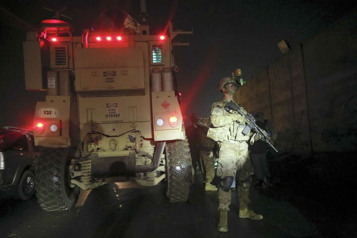 A U.S. soldier stands guard at the site of a suicide attack near a compound belonging to foreigners in Kabul, Afghanistan on Dec. 4, 2016.