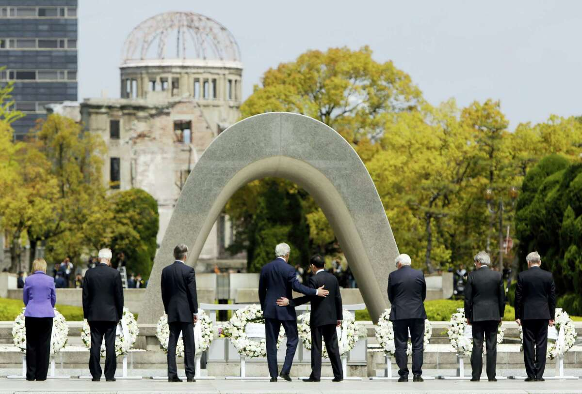 In this April 11, 2016 photo, U.S. Secretary of State John Kerry, fourth from left, puts his arm around Japanese Foreign Minister Fumio Kishida after they and fellow G7 foreign ministers laid wreaths at the cenotaph at Hiroshima Peace Memorial Park in Hiroshima, western Japan. U.S. President Barack Obama will travel to Hiroshima in May 2016 in the first visit by a sitting American president to the site where the U.S. dropped an atomic bomb. Obama's visit will bolster his call for denuclearization and honor victims of the bombing that killed 140,000 Japanese on Aug. 6, 1945.