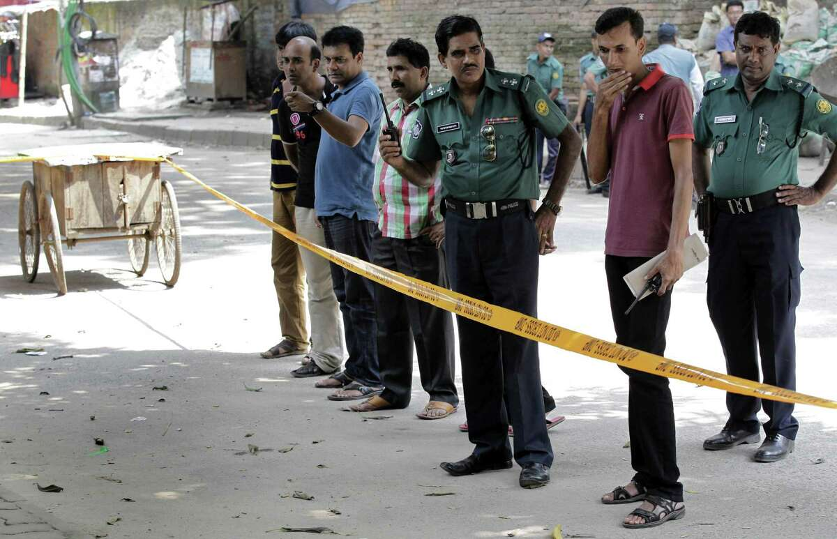 Members of Bangladeshi police and detective branch stand by the site where Italian citizen Cesare Tavella was gunned down by unidentified assailants in Dhaka, Bangladesh, Tuesday, Sept. 29, 2015. The Islamic State militant group claimed responsibility for gunning down the Italian citizen on the street in the diplomatic quarter of Bangladesh's capital, according to an intelligence group monitoring jihadist threats.
