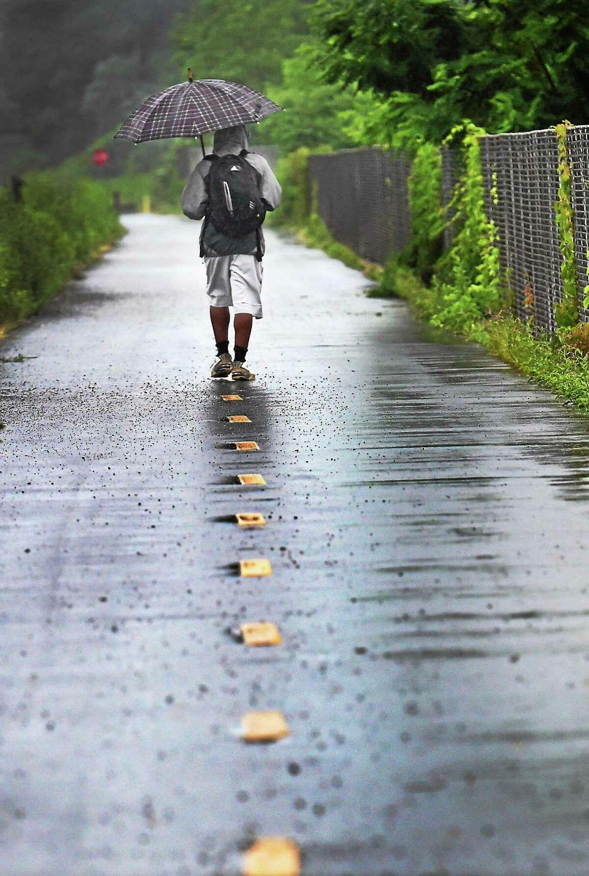 Cedric Gamble of Hamden, 30, walks in the rain June 15 along the Farmington Canal Trail near Treadwell St. in Hamden.
