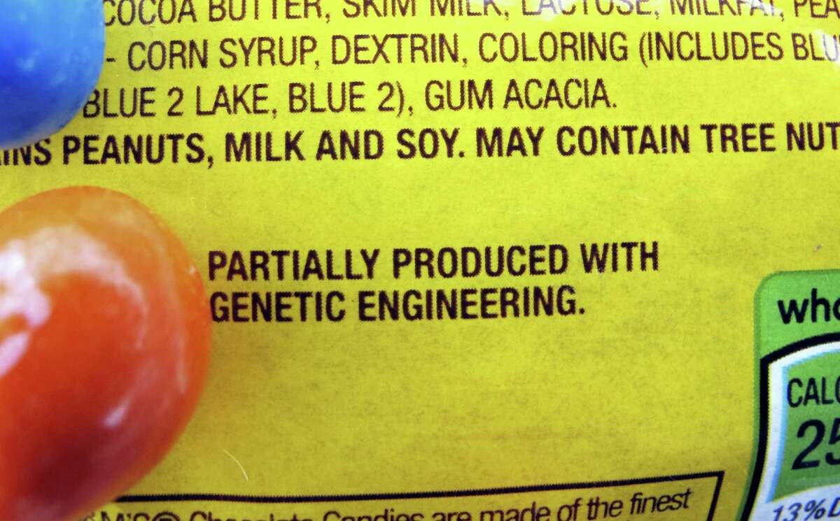 """In this April 8, 2016 photo, a new disclosure statement is displayed on a package of Peanut M&M's candy in Montpelier, Vt., saying they are """"Partially produced with genetic engineering."""""""