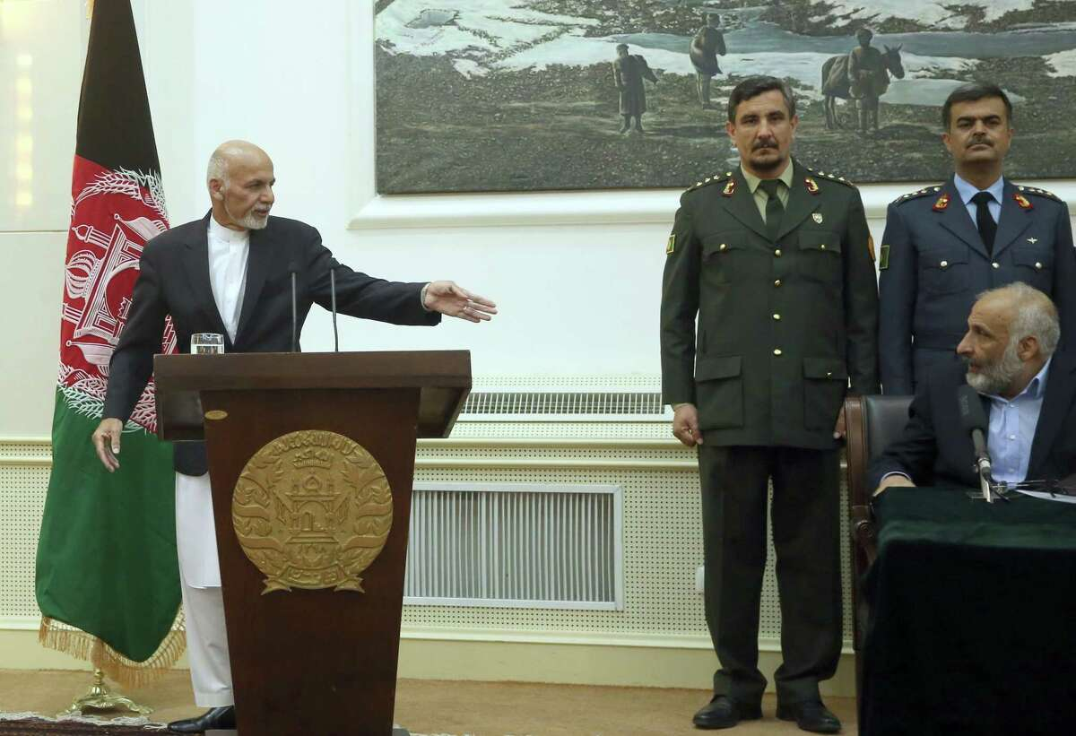 Afghan President Ashraf Ghani, left, points Afghanistan's acting defense minister Masoom Stanikzai, sitting, during a press conference at presidential palace in Kabul, Afghanistan, Tuesday, Sept. 29, 2015. Taliban gunmen fanned out in full force Tuesday across a key Afghan city they captured the day before, as the U.S. military carried out an airstrike on Kunduz and President Ashraf Ghani vowed to take the northern city back from the insurgents, urging his nation to trust Afghan troops to do the job.