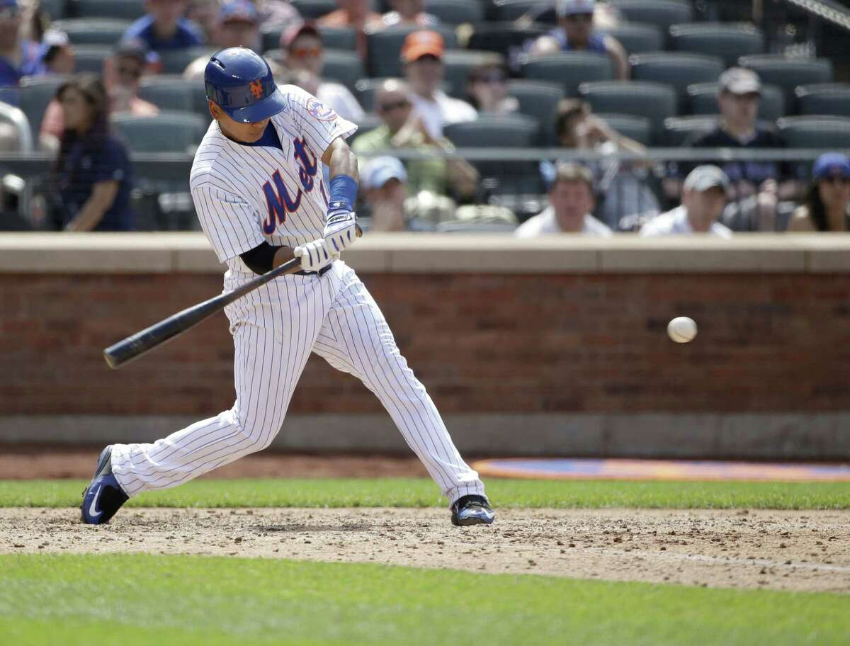 The Mets' Ruben Tejada hits an RBI-double during the seventh inning Sunday against the Marlins.