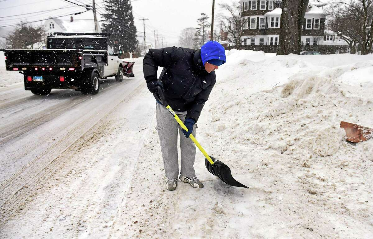 (Arnold Gold-New Haven Register) Victor Erazo shovels snow and ice in front of his home on Wakelee Ave. in Ansonia on 2/9/2015.
