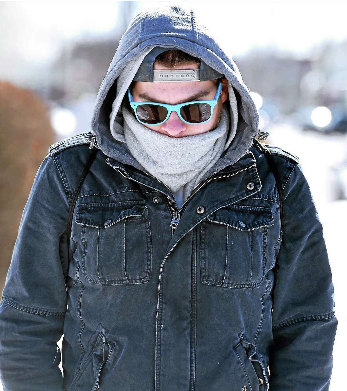 In this file photo from Feb. 13, Sam Vitale of West Haven tries to stay warm walking home along Campbell Avenue in West Haven.