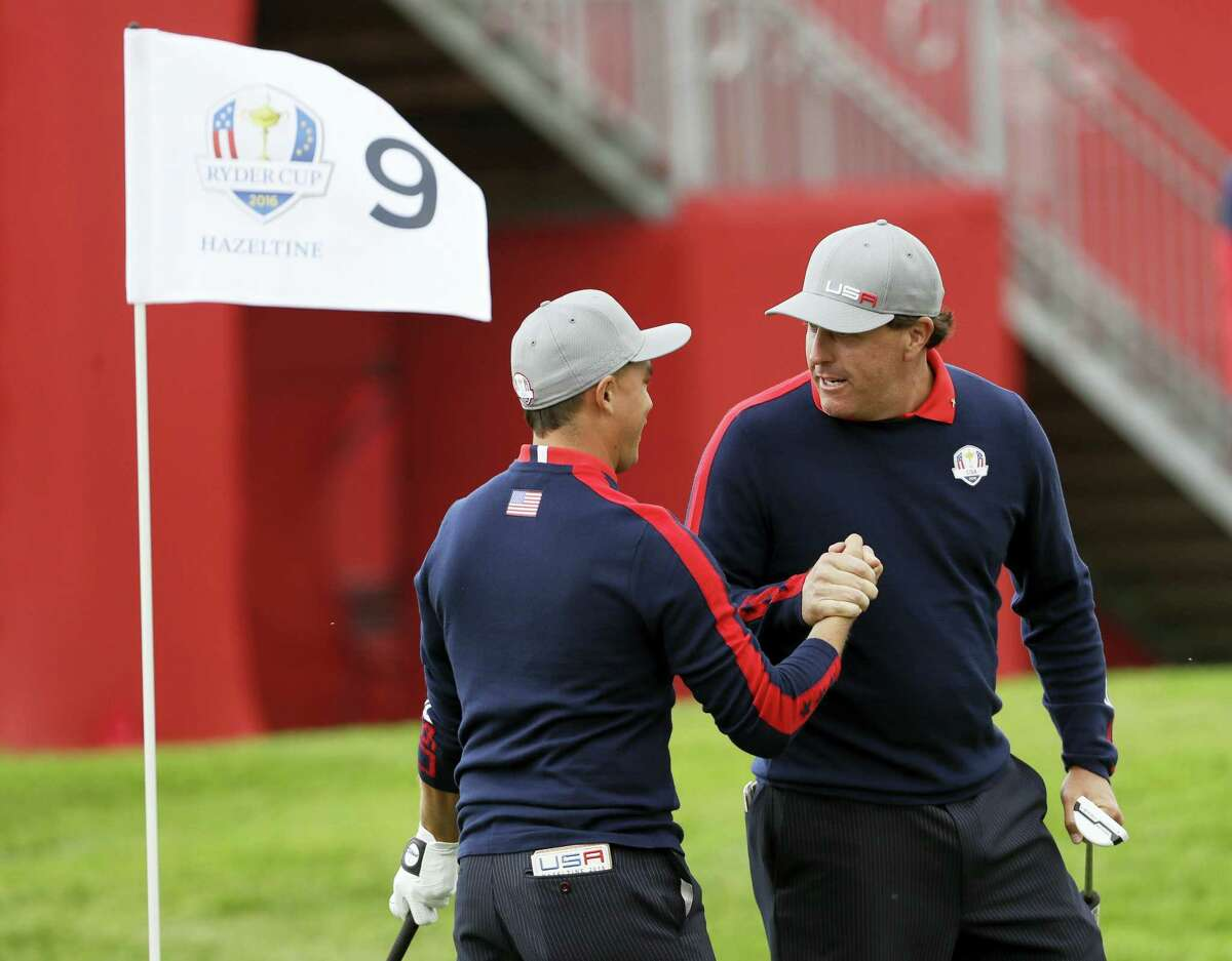Phil Mickelson celebrates with teammate Rickie Fowler after Fowler chipped in on the ninth to win the hole during the Ryder Cup on Friday.