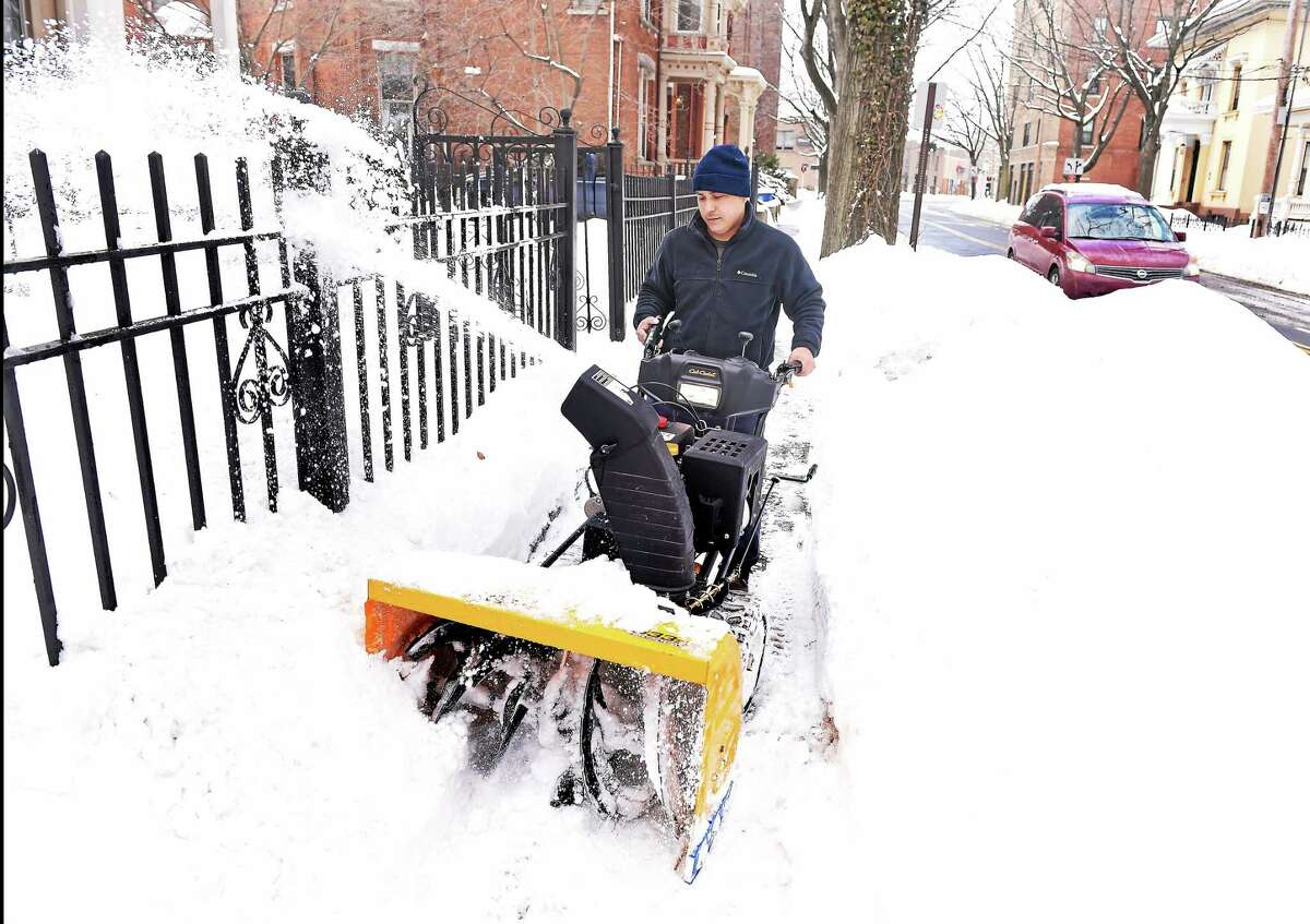 Walter Lapara clears snow from a sidewalk on Chapel Street in New Haven Monday.