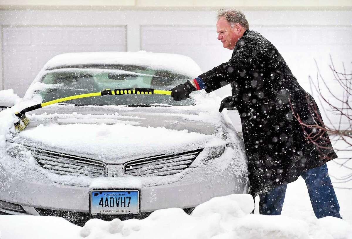 Jeff Teplitzky clears snow from his car in Milford Sunday, the first day of March. Februrary ended up the coldest month on record in Connecticut.