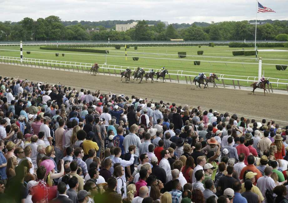 In this June 8, 2013 photo, fans cheer race horses as they near the finish line at Belmont Park in Elmont, N.Y. Photo: AP Photo/Seth Wenig, File  / AP