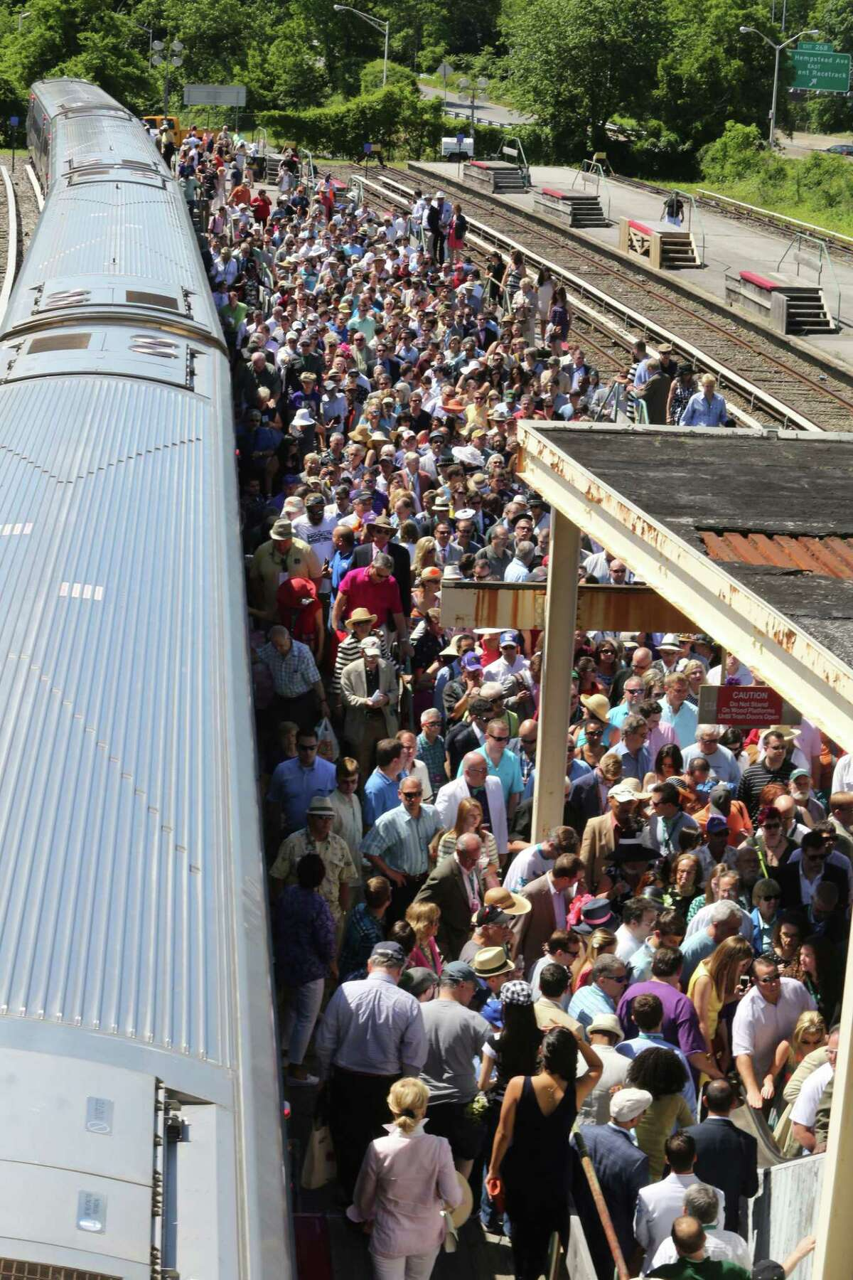 In this June 7, 2014 photo, horse racing fans pile out of the Long Island Railroad for the Belmont Stakes horse race, in Elmont, N.Y.
