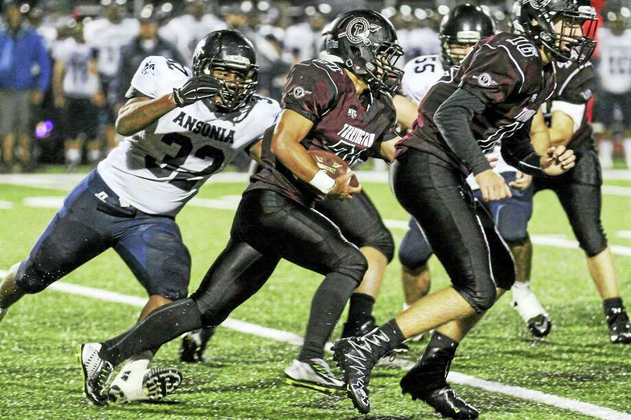 While Ansonia ran wild, Torrington's normally-strong running attack had nowhere to go Friday night as Ansonia's Malcolm Martin closes in on ball carrier Dom Phengkaen. Photo: Photo By Marianne Killackey  / 2015