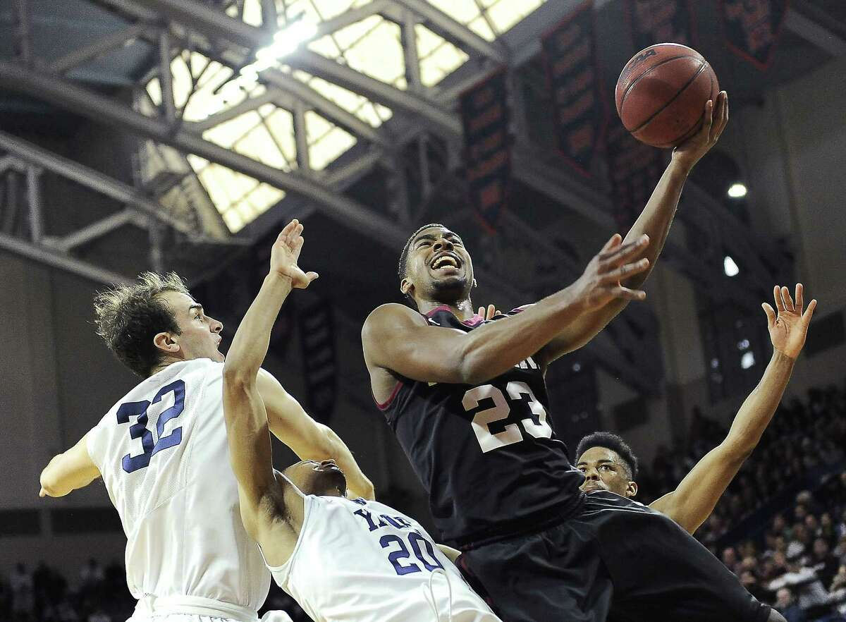 Harvard's Wesley Saunders (23) drives to the basket and shoots over Yale's Javier Duren (20) and Greg Kelley (32) during the Crimson's 53-51 win in an Ivy League playoff game on Saturday in Philadelphia.