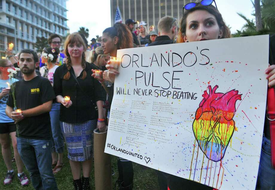Macaila Fernandes, of Orlando, Fla. holds a poster as she joins a candlelight vigil at Lake Eola Park in Orlando, Fla. on June 19, 2016. Photo: Craig Rubadoux/Florida Today Via AP  / USA Today / Florida Today