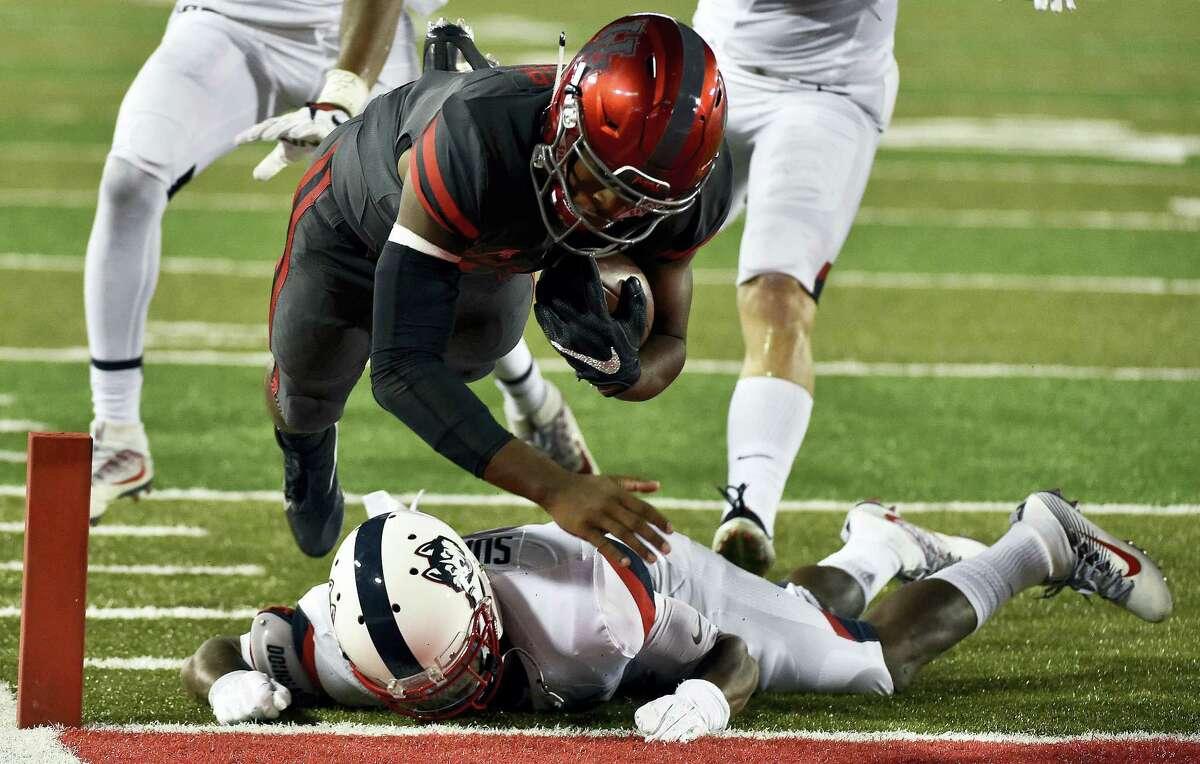 Houston quarterback Greg Ward Jr., top, leaps over UConn cornerback Jamar Summers to score during Thursday night's game.