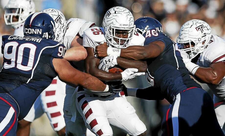 Connecticut defensive tackle Julian Campenni (90) and linebacker Marquise Vann (46) tackle Temple running back Jamie Gilmore (26) during the first quarter of an NCAA college football game in East Hartford, Conn., Saturday, Sept. 27, 2014. (AP Photo/Michael Dwyer) Photo: AP / AP