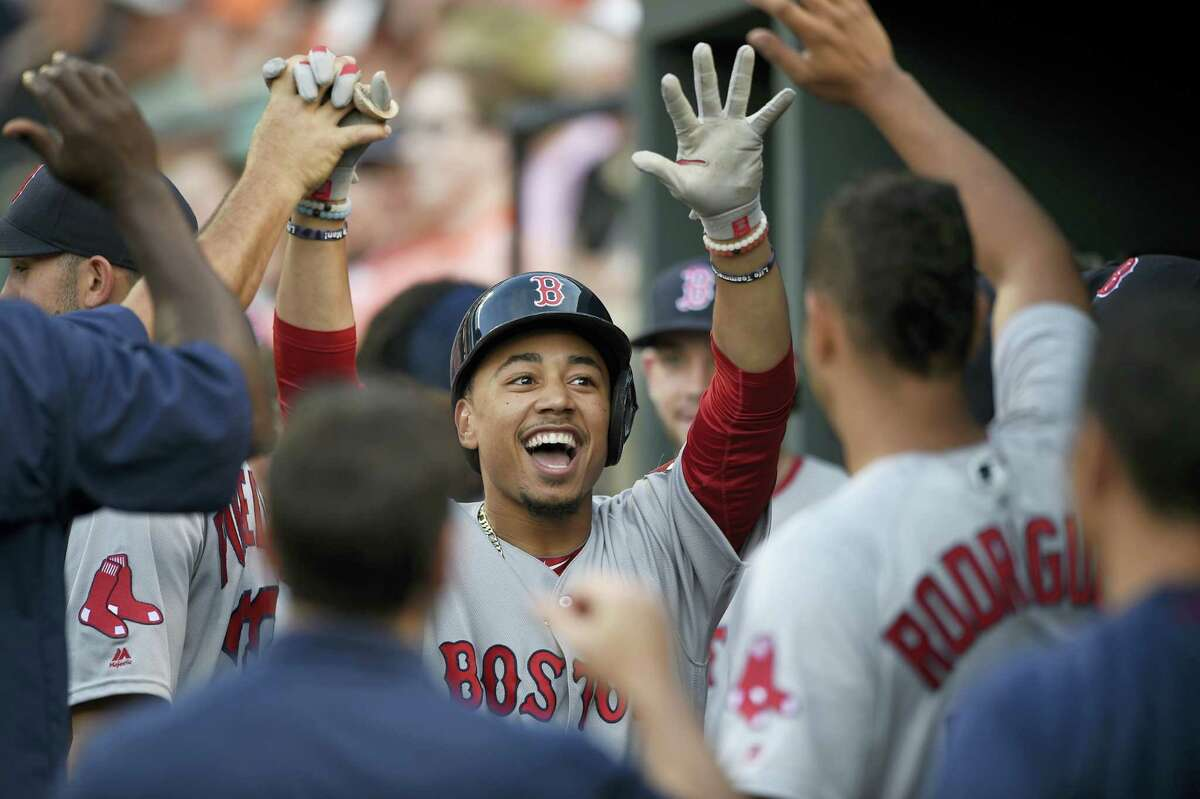 Boston Red Sox' Mookie Betts celebrates his home run in the dugout during the first inning against the Baltimore Orioles, Tuesday, May 31, 2016, in Baltimore. Betts homered three times in the 6-2 victory.