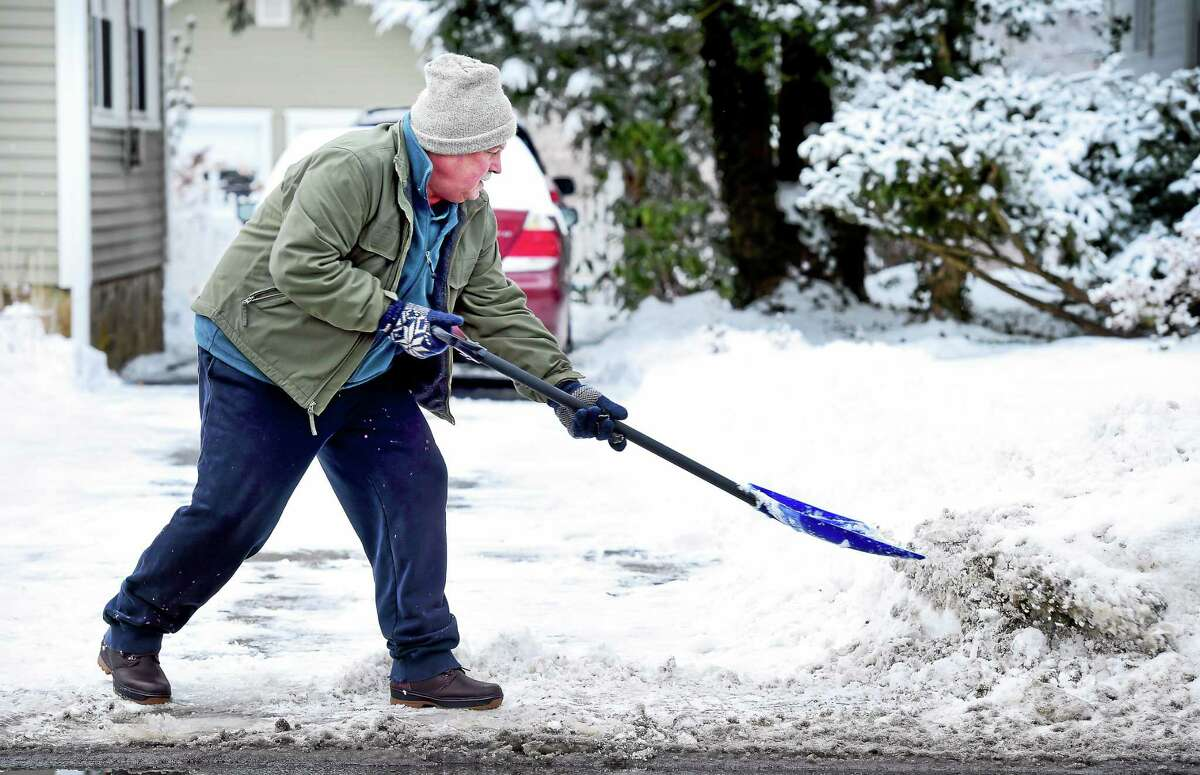 Dennis Paillard shovels his driveway in Milford Friday.