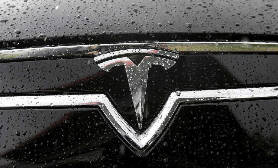A Tesla symbol is shown on a car outside of the Tesla factory in Fremont, Calif., Thursday, May 14, 2015. (AP Photo/Jeff Chiu) Photo: AP / AP