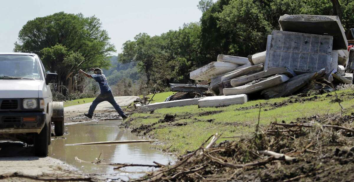 Johnny Rodriguez leaps over standing water as he works along the Blanco River, Friday, May 29, 2015, in Wimberley, Texas. Search efforts continue for those persons who went missing from the Memorial Day weekend floods in Central Texas. (AP Photo/Eric Gay)