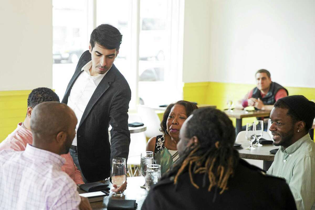 """Co-owner Cristian Mora serves costumers recently at Girard a """"No-Tip"""" restaurant in Philadelphia."""