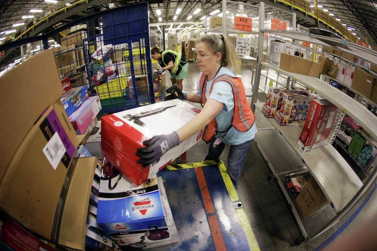 In this Dec. 1, 2014, photo, Teresa Clark fills an order at the Amazon fulfillment center in Lebanon, Tenn.