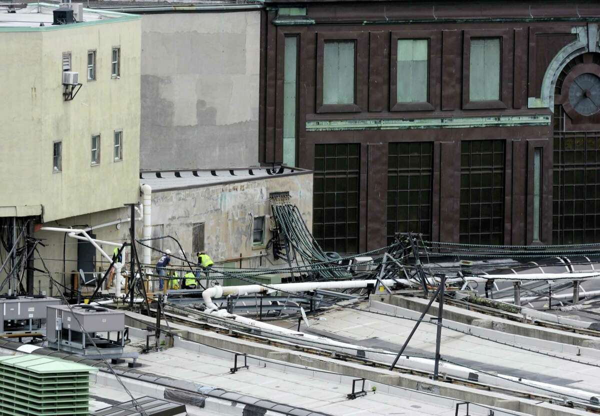 Workers examine a section of the roof at the Hoboken station where a train crashed into the building, Thursday Sept. 29, 2016 in Hoboken, N.J. A rush-hour commuter train crashed through a barrier at the busy Hoboken station and lurched across the waiting area Thursday morning, killing one person and injuring more than 100 others in a tangle of broken concrete, twisted metal and dangling wires.