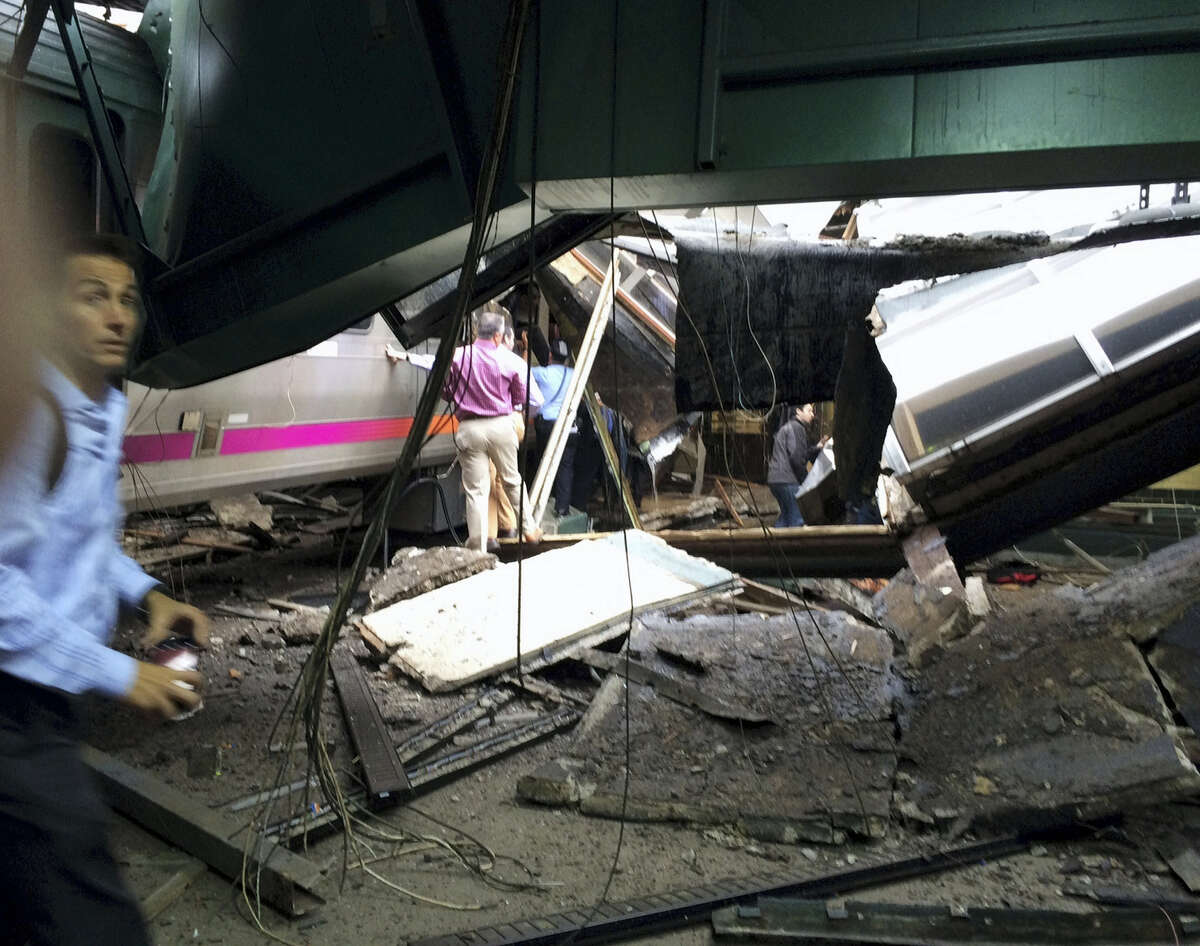 In a photo provided by William Sun, people examine the wreckage of a New Jersey Transit commuter train that crashed into the train station during the morning rush hour in Hoboken,, N.J., Thursday, Sept. 29, 2016. The crash caused an unknown number of injuries and witnesses reported seeing one woman trapped under concrete and many people bleeding.