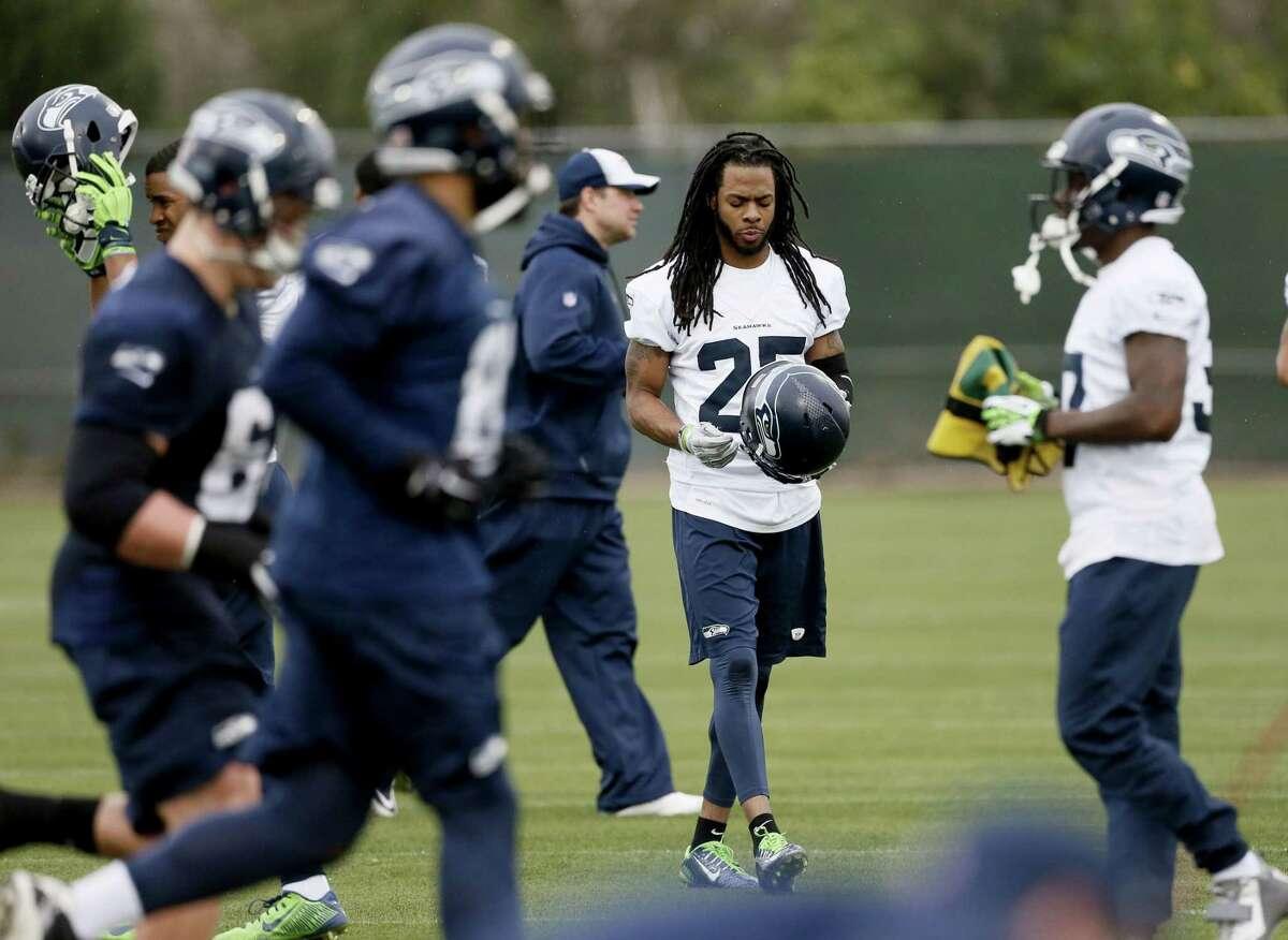 Seattle Seahawks cornerback Richard Sherman puts his helmet on during practice Thursday in Tempe, Ariz.