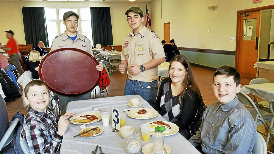 N.F. Ambery photo Boy Scouts of America Troop 35 of Goshen's Ben Roy, 13, and Mason Mangiaracina, 13, serve Angelo DiPippo, 9; Angelo's mother Amy DiPippo; and Angelo's brother, Anthony DiPippo, 12, all of Torrington, at the Goshen breakfast. Photo: Journal Register Co.