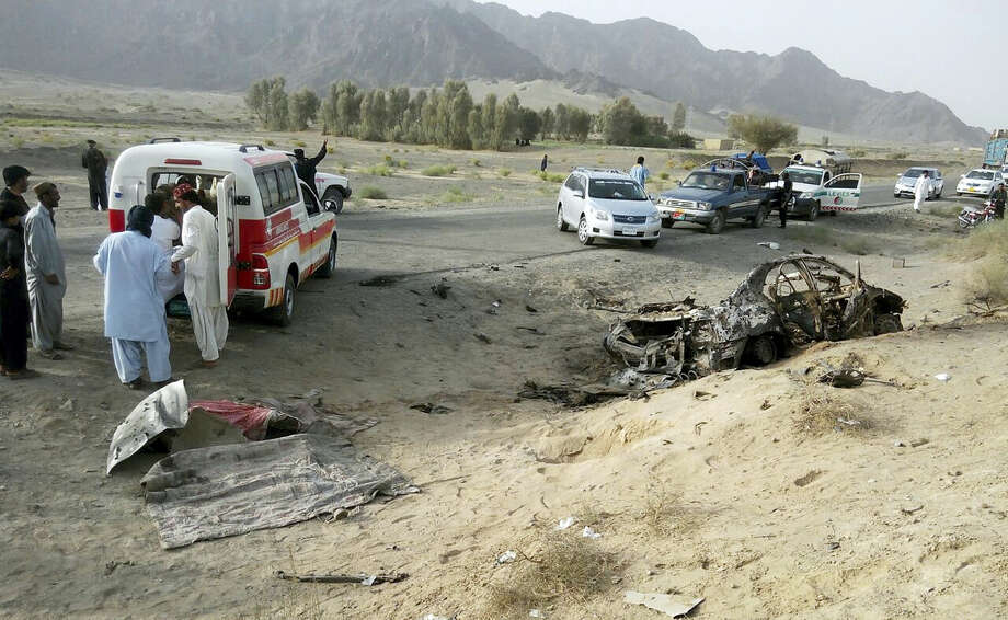 This Saturday, May 21, 2016, file photo taken by freelance photographer Abdul Malik, purports to show volunteers standing near the wreckage of the destroyed vehicle, in which Mullah Akhtar Mansour was allegedly traveling in the Ahmed Wal area in Baluchistan province of Pakistan, near Afghanistan border. The Afghan Taliban has confirmed that its former leader Mullah Akhtar Mansour was killed in a U.S. drone strike last week and appointed a successor. In a statement sent to media Wednesday, May 25, 2016, the insurgent group said its new leader is Mullah Haibatullah Akhundzada, one of two Mansour's deputies. Photo: AP Photo/Abdul Malik, File   / AP