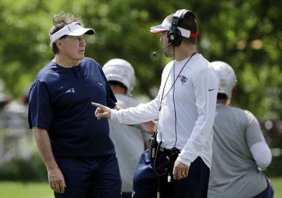 New England Patriots head coach Bill Belichick, left, speaks with offensive coordinator Josh McDaniels during an organized team activity on Friday in Foxborough, Mass. Photo: Elise Amendola — The Associated Press  / AP