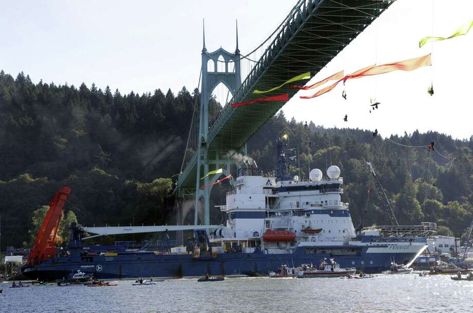 In this July 30, 2015 photo, the Royal Dutch Shell PLC icebreaker Fennica heads up the Willamette River under protesters hanging from the St. Johns Bridge on its way to Alaska in Portland, Ore. Royal Dutch Shell will cease exploration in Arctic waters off Alaska's coast following disappointing results from an exploratory well backed by billions in investment and years of work. Photo: AP Photo/Don Ryan, File  / AP