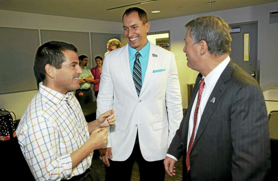 Cheshire's Nick Carparelli, center, is shown here prior to a 2013 press conference in Miami to announce the annual Miami Beach Bowl. Register columnist Chip Malafronte says Carparelli should be a strong candidate to be Warde Manuel's replacement as UConn's athletic director. Photo: The Associated Press File Photo  / AP
