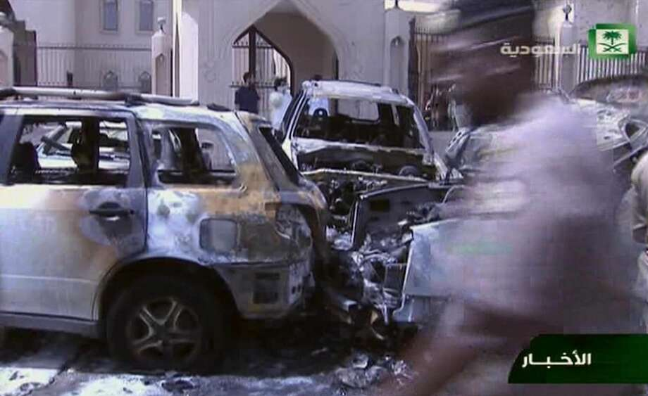 In this still image taken from video provided by Saudi TV, burnt out cars are seen in the aftermath of a suicide bomb outside the the Imam Hussein mosque in the port city of Dammam, Saudi Arabia, Friday, May 29, 2015.  A suicide bomber blew himself up in the parking lot of a Shiite mosque in eastern Saudi Arabia during Friday prayers, killing four people in the second such attack in as many weeks claimed by the Islamic State group. (Saudi Television via AP) SAUDI ARABIA OUT Photo: AP / SAUDI TV