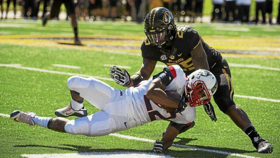 UConn running back Arkeel Newsome, bottom, is tackled by Missouri linebacker Donavin Newsom on Sept. 19. Photo: The Associated Press File Photo  / FR23535 AP