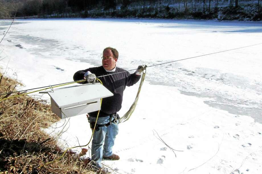 The late Bill Rundall, former chairman of the Housatonic River Ice Watch, set up equipment in Kent in previous years. Boxes are located around town for locals to enter their guess. Photo: Courtesy Photos