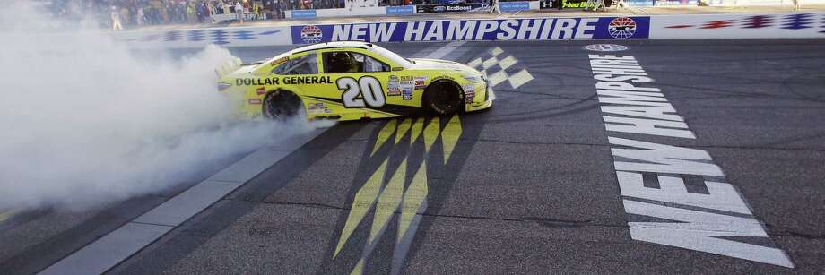 Matt Kenseth celebrates at the finish line after winning the NASCAR Sprint Cup series race at New Hampshire Motor Speedway on Sunday. Photo: Jim Cole — The Associated Press  / AP