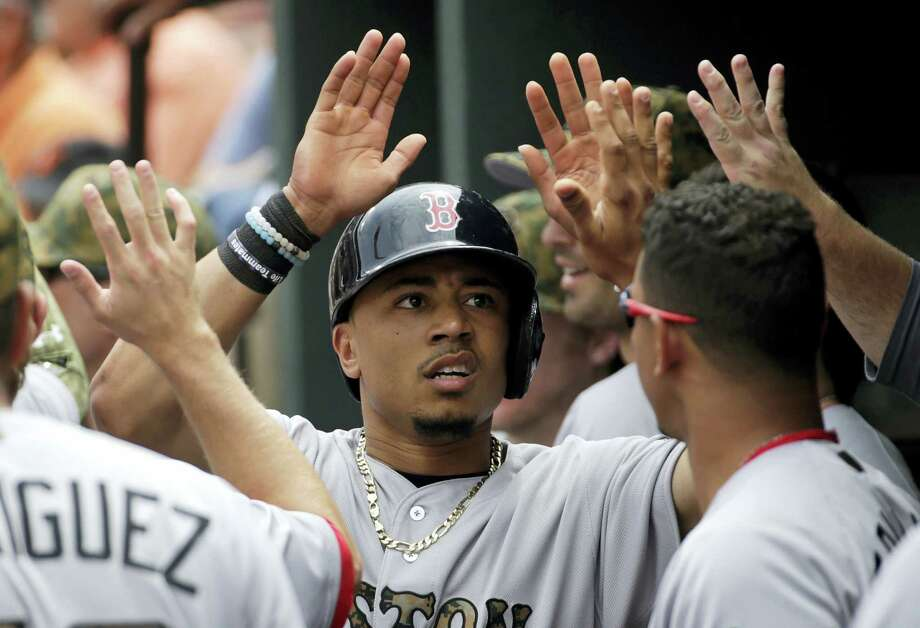Mookie Betts high-fives Red Sox teammates in the dugout after scoring on a groundout by Xander Bogaerts in the first inning in Baltimore Monday. Photo: Patrick Semansky — The Associated Press  / Copyright 2016 The Associated Press. All rights reserved. This material may not be published, broadcast, rewritten or redistribu
