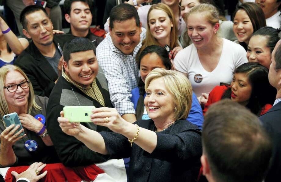 Democratic presidential candidate Hillary Clinton takes a selfie with supporters at a rally Thursday. Photo: ASSOCIATED PRESS  / Copyright 2016 The Associated Press. All rights reserved. This material may not be published, broadcast, rewritten or redistribu